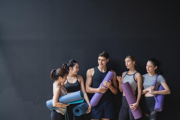 Grupo de raça mista de atletas caucasianos e asiáticos, mulheres e homens na parede preta, esperando para desfrutar da aula de ioga juntos Foto Premium
