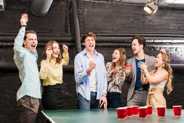 Grupo de rir amigos desfrutando de cerveja pong na mesa Foto gratuita