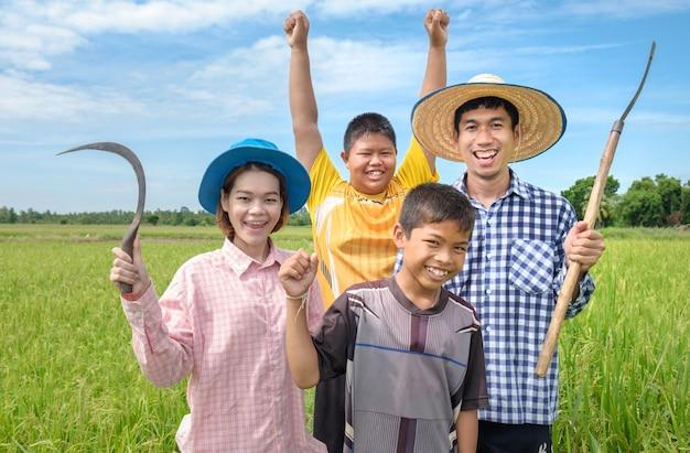 Grupo de rir homem feliz agricultor asiático, mulher e dois filhos sorriam e segurando ferramentas no campo de arroz verde Foto Premium