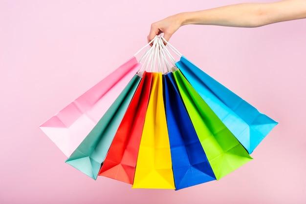 Grupo de sacos coloridos sendo realizada Foto gratuita