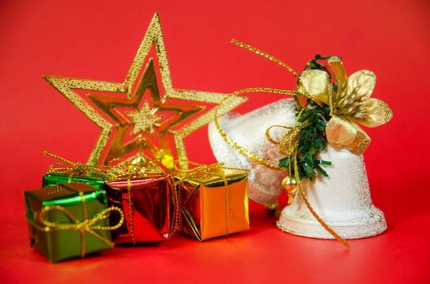 Grupo de sino, presente e estrela no natal em fundo vermelho Foto Premium