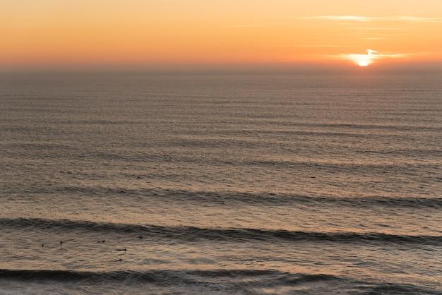 Grupo de surfistas esperando por uma onda no meio do mar com o sol ao entardecer no fundo Foto Premium
