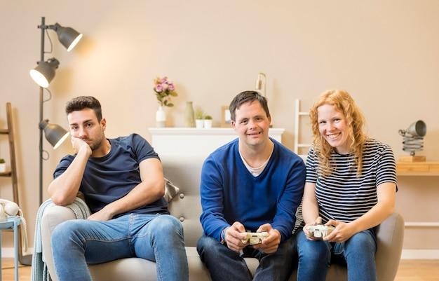 Grupo de três amigos jogando videogame em casa Foto gratuita