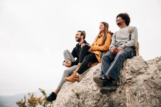 Grupo de três amigos, sentado no topo do pico da montanha olhando a vista Foto gratuita