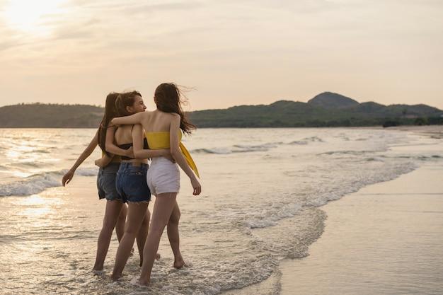 Grupo de três jovens mulheres asiáticas caminhando na praia Foto gratuita