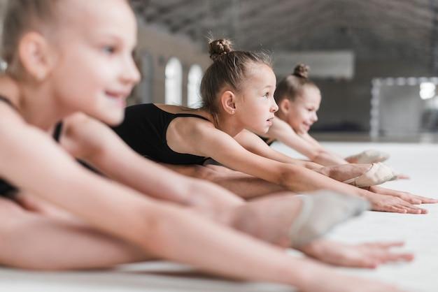 Grupo de três meninas de bailarinas sentada no chão, estendendo-se para a frente na pista de dança Foto gratuita