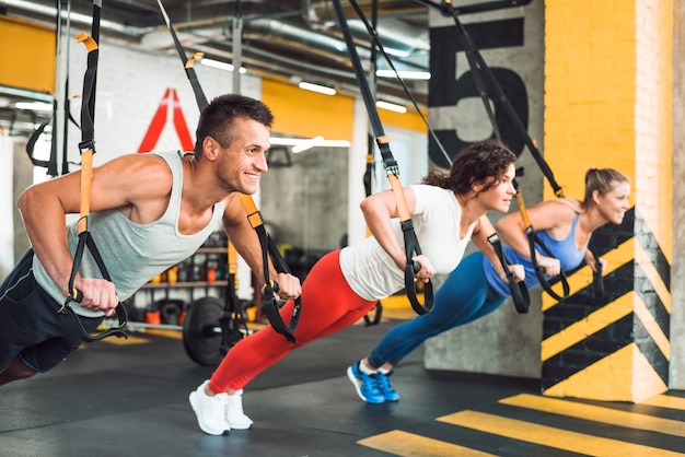 Grupo de um povo atlético, exercitando com cinta de aptidão no filhote de saúde Foto gratuita