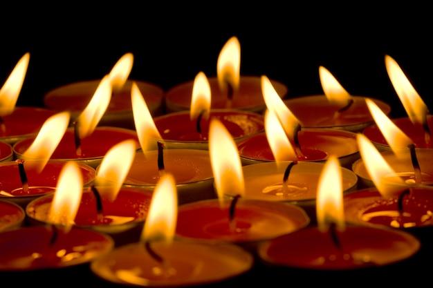 Grupo de velas em chamas no fundo escuro Foto Premium