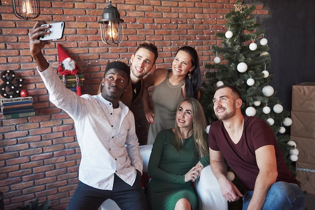 Grupo de velhos amigos se comunica e faz uma foto de selfie. ano novo está chegando. celebre o ano novo em um ambiente acolhedor Foto Premium