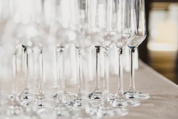 Grupo de vidros vazios e transparentes do champanhe em um restaurante. grupo de vidros vazios e transparentes do champanhe em um restaurante. Foto Premium