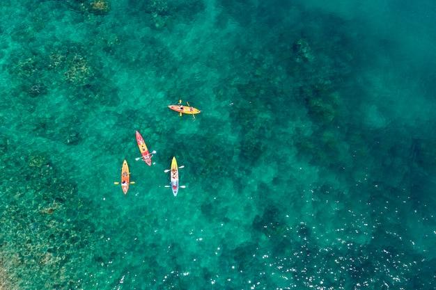 Grupo de vista aérea do viajante de caiaque na praia Foto Premium