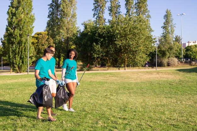 Grupo de voluntários ecológicos saindo do parque após a limpeza dos gramados Foto gratuita