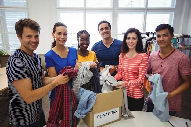 Grupo de voluntários verificando roupas Foto gratuita