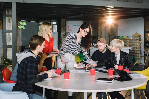 Grupo diversificado multiétnico de equipe criativa, empresários casuais ou estudantes universitários em reunião estratégica ou discussão de projeto no escritório, usando tablets. conceito de inicialização ou trabalho em equipe. Foto Premium