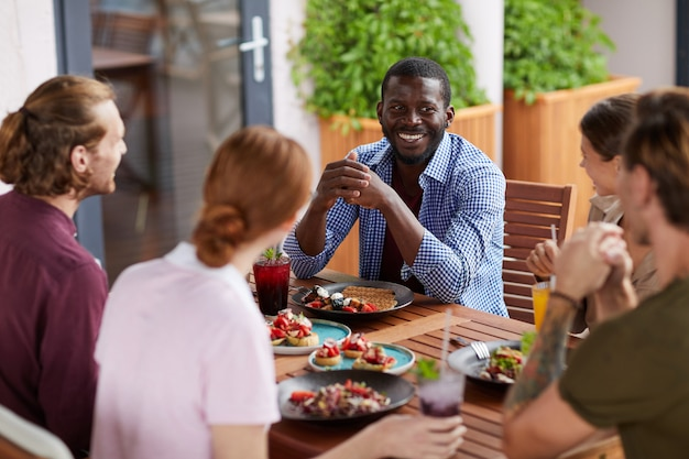 Grupo diverso de amigos, aproveitando o almoço juntos Foto Premium