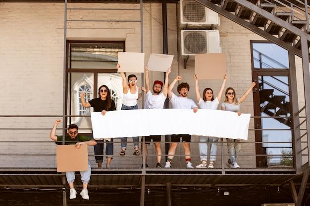 Grupo diverso de pessoas que protestam com sinais em branco. protesto contra os direitos humanos, abuso de liberdade, questões sociais Foto gratuita