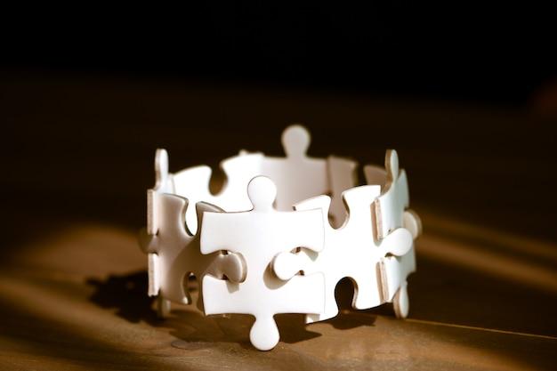 Grupo do enigma de serra de vaivém branco na tabela de madeira. trabalho em equipe de negócios e colaborar conceito. Foto Premium