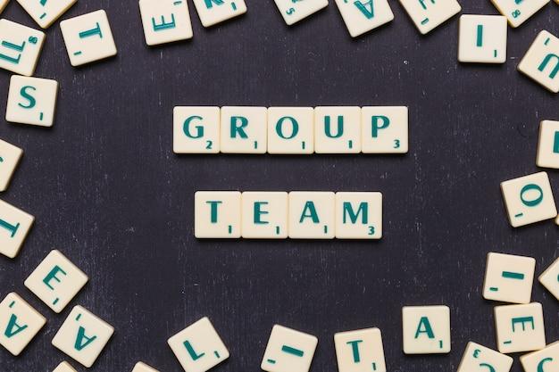 Grupo equipe scrabble letras sobre fundo preto Foto gratuita