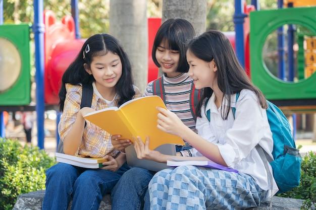 Grupo estudante jovens e livro de leitura de educação no parque da cidade Foto Premium