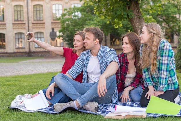 Grupo estudantes, sentando, perto, árvore Foto gratuita