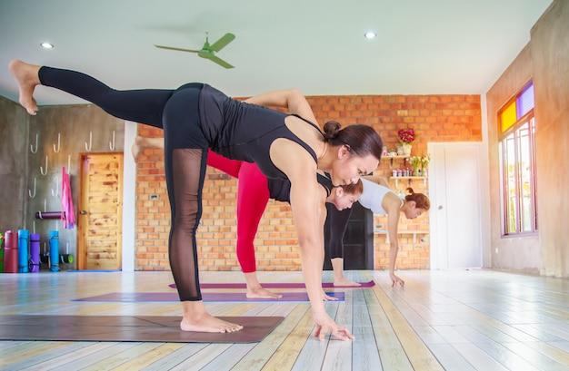Grupo fêmea asiático da aptidão que faz a pose da ioga do namaste na fileira na classe da ioga. foco seletivo Foto Premium