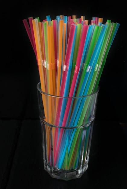 Grupo isolado de palhas plásticas da cor em um vidro em um fundo preto. verão, equipamentos do festival. Foto Premium