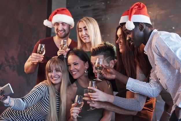 Grupo jovens bonitos fazendo selfie na festa de ano novo, melhores amigas meninas e meninos juntos se divertindo, posando de pessoas em estilo de vida emocional. chapéus de papai noel e taças de champanhe nas mãos Foto Premium