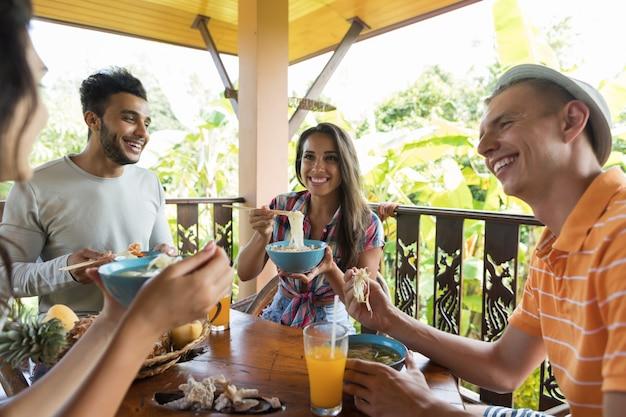 Grupo jovens, falando, enquanto, comendo macarronada sopa amigos tradicional, cozinha asiática, jantar, togeth Foto Premium