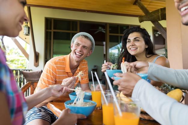 Grupo jovens, falando, enquanto, comer, noodles, sopa, tradicional, asiático, alimento Foto Premium