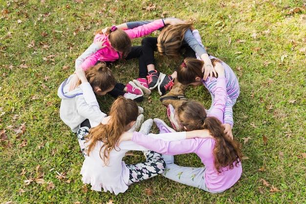 Grupo meninas, sentar-se, em, huddle, ligado, grama verde Foto gratuita