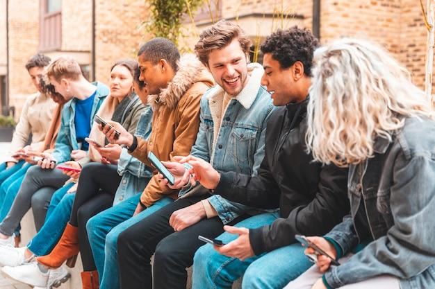 Grupo multicultural de amigos usando smartphone e se divertindo Foto Premium