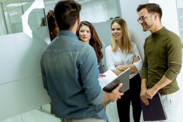 Grupo multiétnico de jovens em pé no escritório moderno e de brainstorming Foto Premium