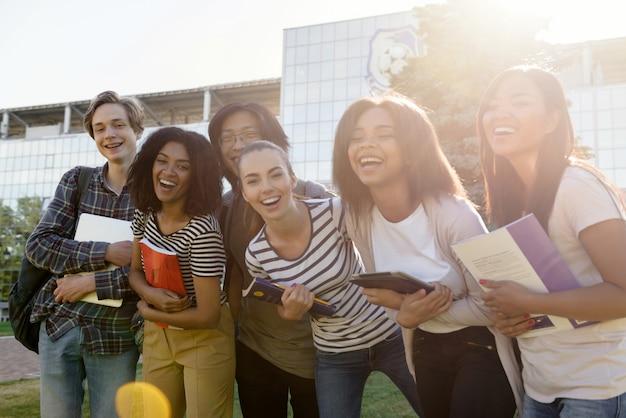 Grupo multiétnico de jovens estudantes alegres em pé ao ar livre Foto gratuita