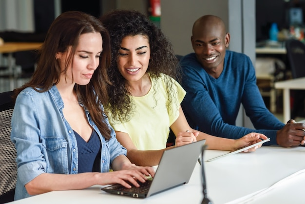 Grupo multiétnico de jovens que estudam com laptop Foto gratuita