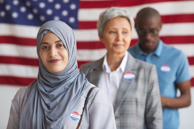 Grupo multiétnico de pessoas na seção eleitoral no dia da eleição, foco na mulher árabe sorridente com o adesivo votei, copie o espaço Foto Premium