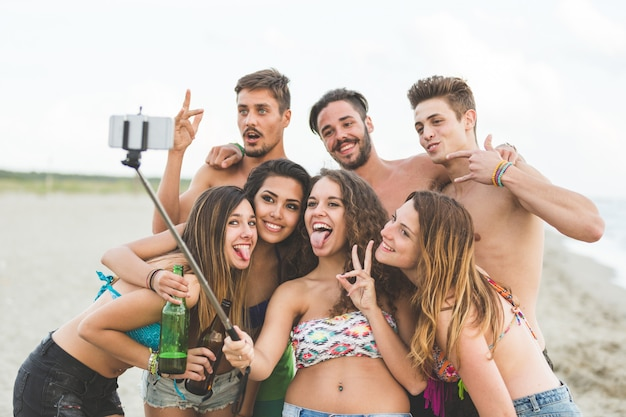 Grupo multirracial de amigos tomando selfie na praia Foto Premium