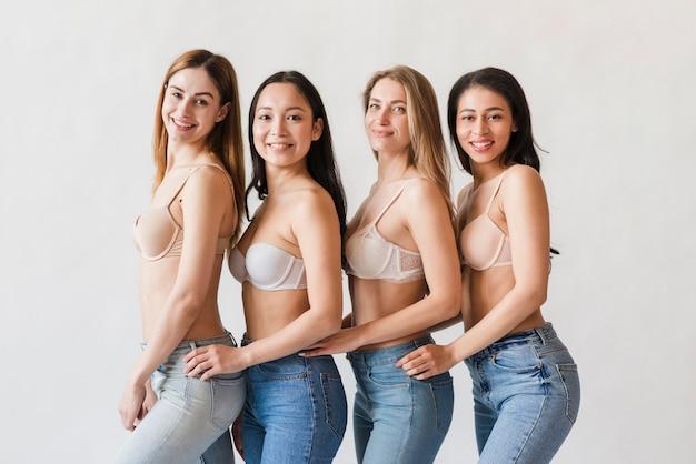 Grupo multirracial de mulheres felizes posando em sutiãs Foto gratuita