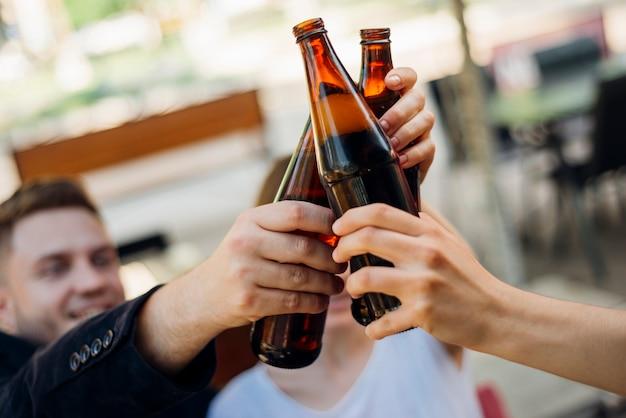 Grupo pessoas, clanging, garrafas, junto Foto Premium