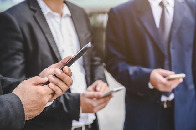 Grupos de negócios estão usando telefones celulares para fazer contatos comerciais, comércio, comunicações, ações, finanças, tecnologia. Foto Premium