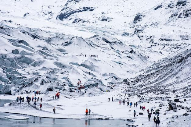 Grupos de turistas caminhadas trekking nas montanhas rochosas brancas nevadas Foto gratuita