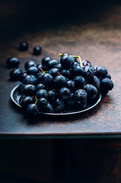 Grupos de uvas vermelhas maduras frescas em um fundo estrutural da tabela da bandeja do metal. uvas escuras, uvas azuis Foto Premium