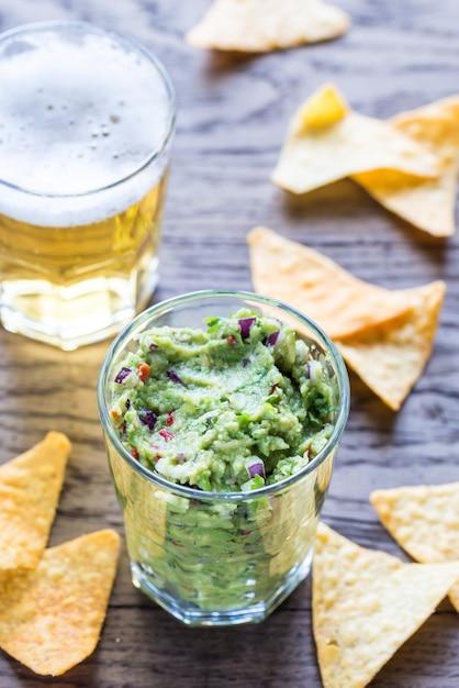 Guacamole com tortilla chips e copo de cerveja Foto Premium