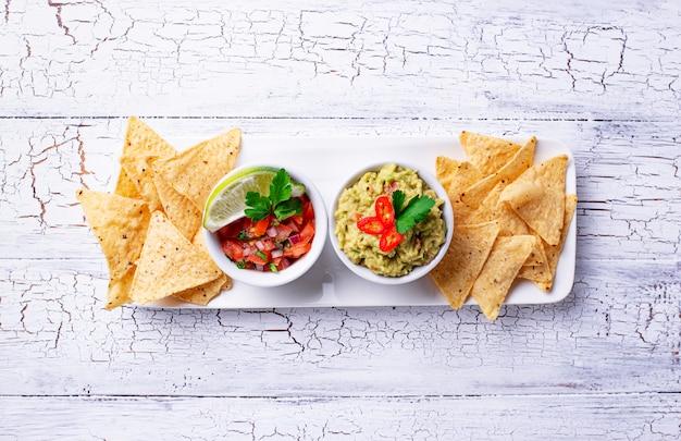 Guacamole, salsa molho de tomate e nachos chips Foto Premium