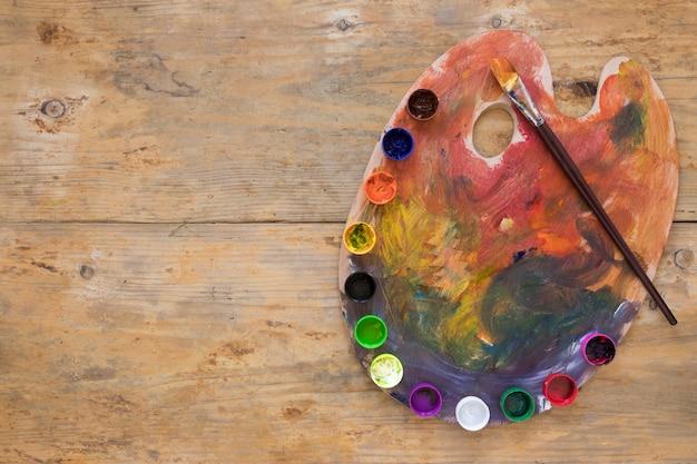 Guache multicolorido colocado na paleta com pincel Foto gratuita