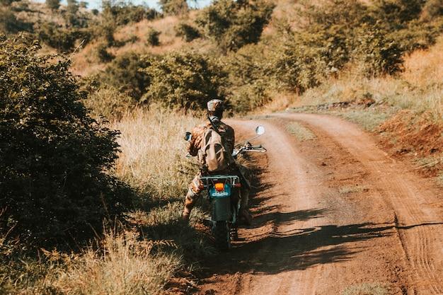 Guarda anti-caça furtiva em uma motocicleta, em uma estrada de terra Foto gratuita