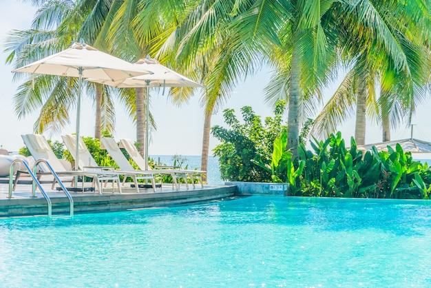 Guarda-chuva com cadeira no resort de piscina do hotel Foto gratuita