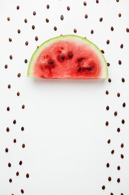 Guarda-chuva de melancia plana leigos com sementes no fundo branco Foto gratuita