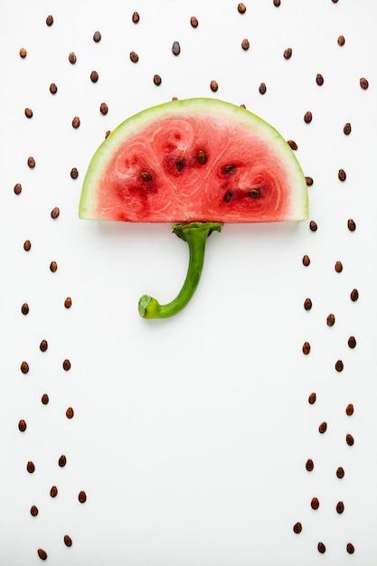 Guarda-chuva de melancia vista superior com sementes no fundo branco Foto gratuita