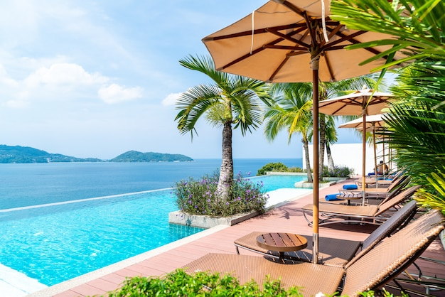 Guarda-chuva e cadeira ao redor da piscina no hotel e resort Foto Premium