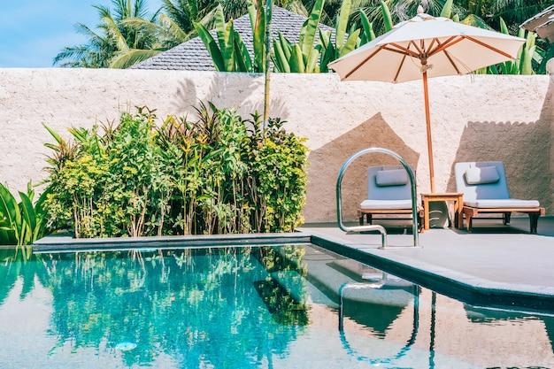 Guarda-chuva e cadeira ao redor da piscina perto da praia do mar oceano com céu azul e nuvem branca Foto gratuita